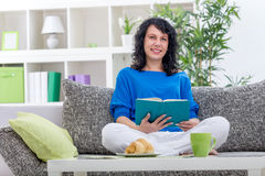 Girl resting at home sitting on the sofa reading a book Stock Images