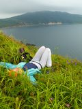 Girl resting on the meadow. Sea landscape with hiking girl lyling on the meadow grass and flowers Stock Photography