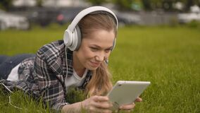 The girl is resting in the park. The girl listens to music in large headphones on nature and scrolls the news on the