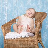 Girl resting in rattan chair Stock Photo