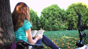 Girl resting and reading at the park stock footage