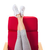 Girl resting in the red chair with her legs up Royalty Free Stock Photo