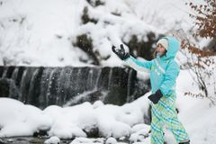 Girl resting on a rock at a winter waterfall stock photos