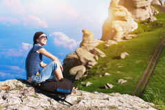 Girl is resting sitting on the grass in mountains Stock Photography
