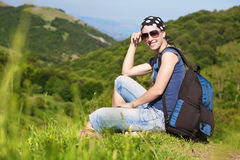 Girl is resting sitting on the grass in mountains Royalty Free Stock Photos