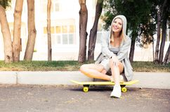 Girl resting with skateboard outdoors Royalty Free Stock Photos