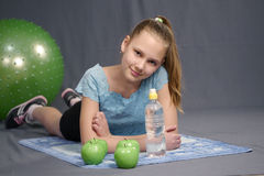 Girl resting on sporting activities. 12 years old girl resting on the sporting activities with a water bottle Stock Image