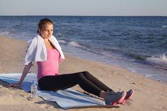 Girl resting after sports. Sitting near the sea Stock Photos