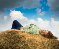 Girl  resting on straw bale Stock Photography
