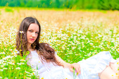 Girl resting in summer field with flowers Royalty Free Stock Photography
