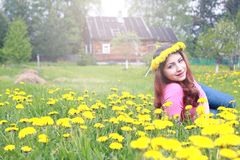 Girl resting on a sunny day in meadow of yellow dandelions Royalty Free Stock Images