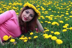 Girl resting on a sunny day in meadow of yellow dandelions Stock Photography