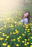 Girl resting on a sunny day in meadow of yellow dandelions Stock Photo
