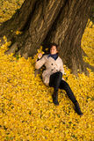 Girl resting under Ginkgo tree Royalty Free Stock Image