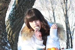 Girl resting in a winter forest, eating cake and drinking tea Royalty Free Stock Photo