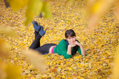Girl  resting on yellow autumn leaves Royalty Free Stock Images