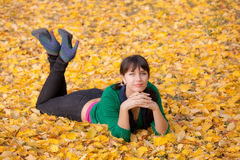 Girl  resting on yellow autumn leaves Stock Photos
