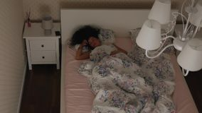 Girl restlessly sleeps on the bed at night Top view. Girl restlessly sleeps on the bed at night. Top view of a sleeping curly woman. Not a healthy dream stock footage