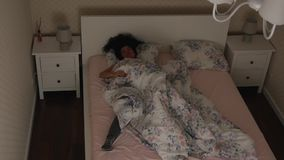 Girl restlessly sleeps on the bed at night Top view. Girl restlessly sleeps on the bed at night. Top view of a sleeping curly woman. Not a healthy dream stock video