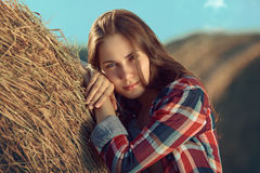 Girl rests against haystack Stock Photos