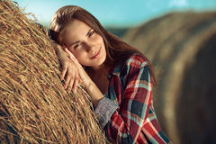 Girl rests against haystack Stock Photo