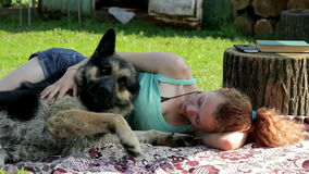 A girl rests with a dog on the grass. On the picnic stock footage
