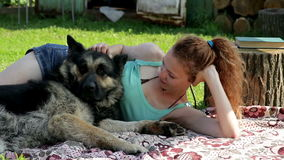 A girl rests with a dog on the grass. On the picnic stock video footage