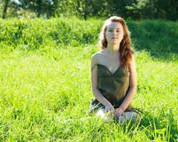 Girl rests in grass meadow Royalty Free Stock Image