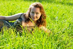 Girl rests in grass meadow Stock Photography