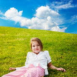 Girl rests in sunny meadow. Young girl looks up while lying in the buttercup strewn grass in a sunny meadow Royalty Free Stock Photography