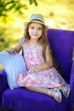 Girl& x27; retrato de s en una silla al aire libre imagen de archivo