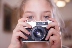 Girl with a retro camera makes a photo, close up royalty free stock images