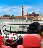 Girl in retro car looking at the landscape of Venice: gondola on Stock Image