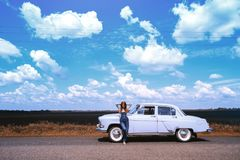 Girl and retro car. Girl stands near a retro car, the background field, and a bright blue sky Stock Images