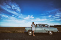 Girl and retro car. Girl stands near a retro car, the background field, and a bright blue sky Stock Photography