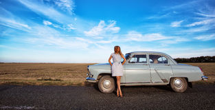 Girl and retro car. Girl stands near a retro car, the background field, and a bright blue sky Royalty Free Stock Photo