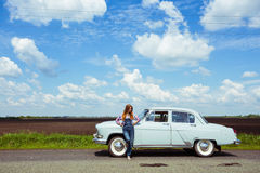 Girl and retro car. Girl stands near a retro car, the background field, and a bright blue sky Stock Photos