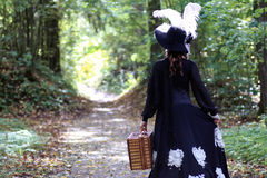 Girl in retro dress 18th century with valise in park Royalty Free Stock Image