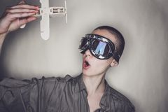 Girl in retro pilot glasses with wooden plane Royalty Free Stock Image