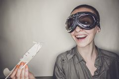 Girl in retro pilot glasses with wooden plane Royalty Free Stock Photography