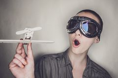 Girl in retro pilot glasses with wooden plane Stock Photos