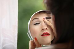 Girl retro style applying make up looking at mirror indoor Royalty Free Stock Images