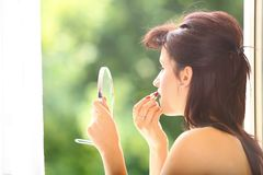 Girl retro style applying make up looking at mirror indoor Royalty Free Stock Photo