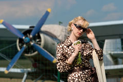 Girl in retro style on background of plane Royalty Free Stock Images
