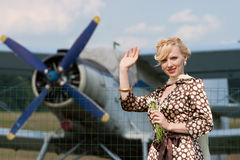 Girl in retro style on background of vintage plane Royalty Free Stock Image
