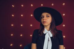 Girl in black dress and black hat posing on red background stock image