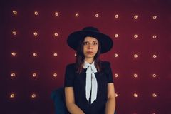 Girl in black dress and black hat posing on red background royalty free stock photos