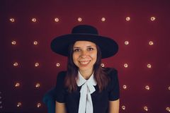 Girl in black dress and black hat posing on red background royalty free stock image
