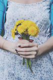 Girl in retro style dress holding bunch of dandelion flowers Stock Photo
