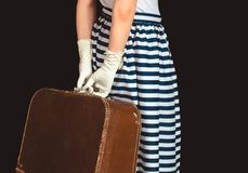 Girl in retro style holds suitcase on black background. Girl in retro style holds vintage suitcase on black background Stock Photography